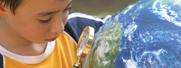 Photo of a child looking at a globe through a magnifying glass